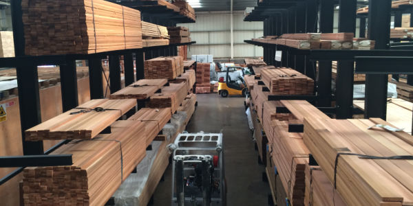 timber warehouse: aisle with racks full of timber packs on both sides