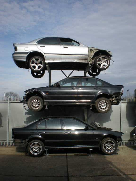 A car rack with three scrap cars on it