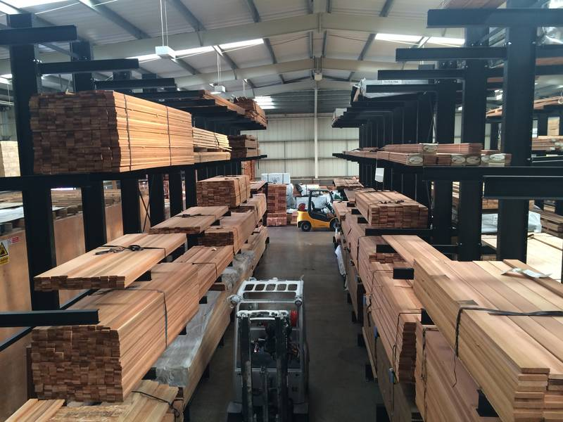 aisle at a warehouse with timber racking on both sides. Forklift truck going up the aisle