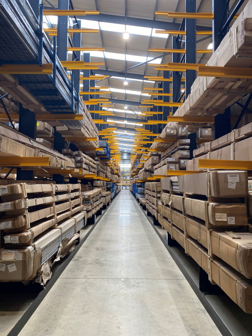 Cantilever racking with blue uprights and yellow arms storing long, boxed items